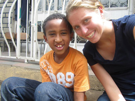 Leak and a Destiny Academy student rest on the steps after a rigorous game of soccer in the schoolyard.