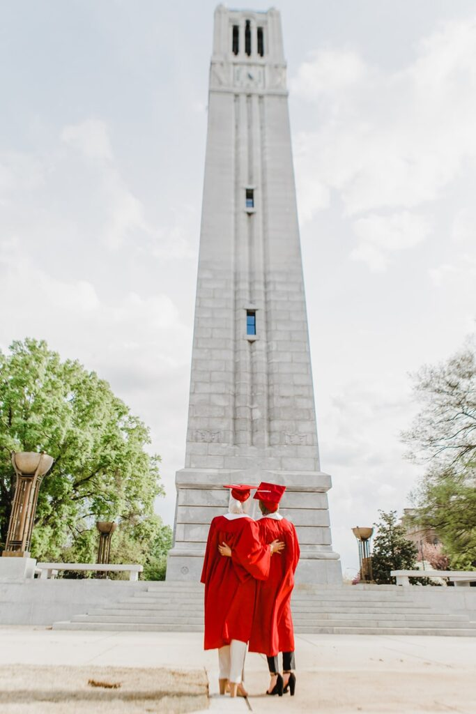 Iman Ibrahim, left, and Salam Ibrahim look up at the Memorial Belltower in their graduation robes.