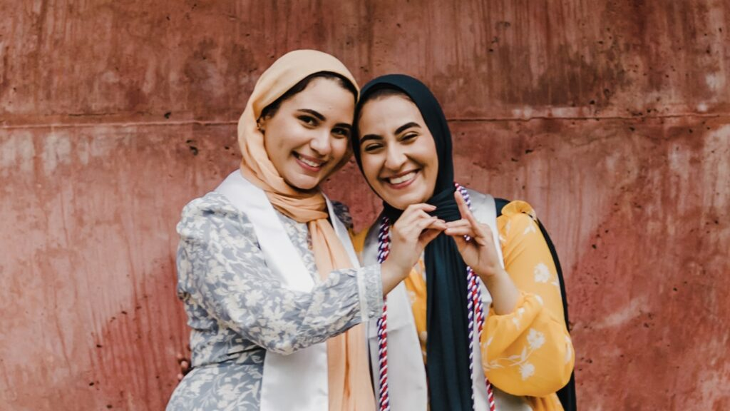 Twin sisters Iman, left, and Salam make wolf hands at the Wolf Ears before graduation.